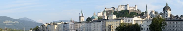 Panorama of houses along the embankment of the Salzach river, mountains and with the Hohensalzburg fortress in Salzburg, Austria.
